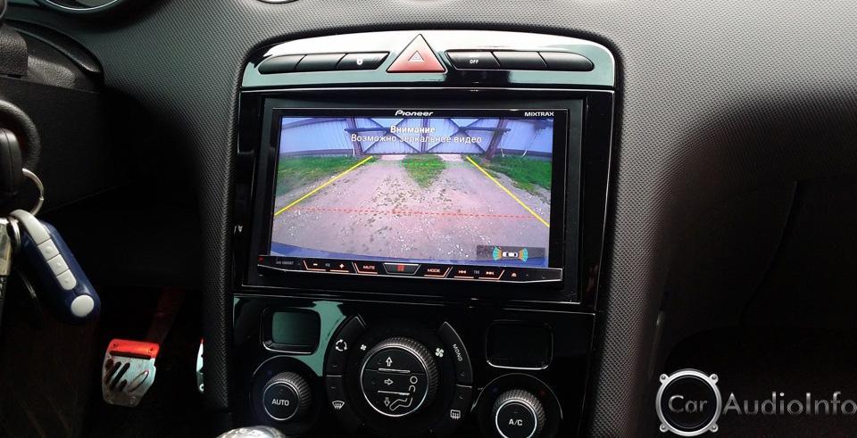 Владелец автомобиля осуществляет парковку задним ходом смотря в монитор